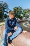 Jugendlicher von 14 Jahren sitzt nahe Brunnen stockfotografie