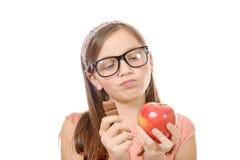 Jugendlicher zögert zwischen Schokolade und einem Apfel stockbild