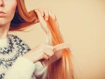 Jugendliches blondes Mädchen, das ihr Haar mit Kamm bürstet Lizenzfreie Stockbilder