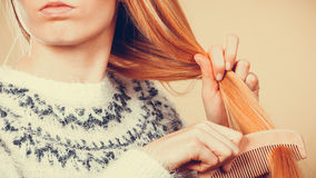 Jugendliches blondes Mädchen, das ihr Haar mit Kamm bürstet Lizenzfreie Stockfotos