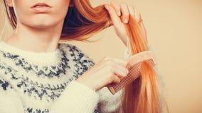 Jugendliches blondes Mädchen, das ihr Haar mit Kamm bürstet Stockfoto