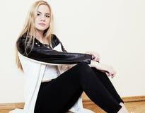 Jugendliches blondes Mädchen der Junge recht, das zu Hause auf Verzweiflung des Bodens sitzt Stockfotos