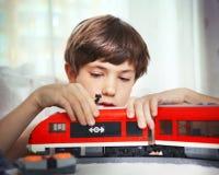 Jugendliches hübsches Jungenspiel mit meccano Spielzeugzug und Eisenbahn sta Stockfotos