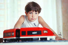 Jugendliches hübsches Jungenspiel mit meccano Spielzeugzug und Eisenbahn sta Stockfotografie