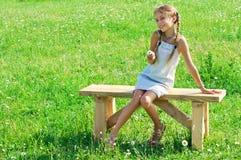 Jugendliches Mädchen auf Bank im Gras stockfoto