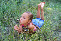 Jugendliches Mädchen, das auf Löwenzahn durchbrennt lizenzfreies stockfoto