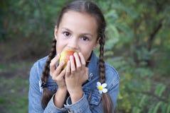 Jugendliches Mädchen, das eine Birne beißt Lizenzfreie Stockfotografie
