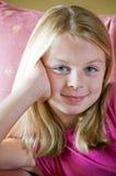 Jugendliches Mädchen, das im Stuhl vor Fenster sitzt Stockfotografie