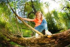 Jugendliches nettes Mädchen, das auf Stamm des gefallenen Baums sitzt Lizenzfreie Stockbilder