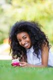 Jugendliches schwarzes Mädchen, das ein Telefon, liegend auf dem Gras - afrikanisches p verwendet Lizenzfreie Stockbilder