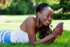 Jugendliches schwarzes Mädchen, das ein Telefon verwendet Stockbild