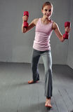 Jugendliches sportives Mädchen tut Übungen mit Dummköpfen, um Muskeln auf grauem Hintergrund zu entwickeln Gesundes Lebensstilkon Lizenzfreie Stockfotografie