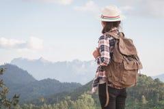Jugendlichetouristen stehen und betrachten die schöne Berglandschaft und schlendern mit einem entspannenden Rucksack auf die Klip lizenzfreie stockfotografie