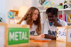 Jugendlichgefühl beteiligt, wenn Metall vom Plastik sortiert wird lizenzfreie stockfotografie