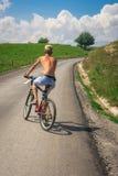 Jugendlichjunge auf Fahrrad auf der Straße außerhalb der Stadt in der Natur Stockfotos