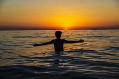 Jugendlichjunge, der auf einem Strand bei Sonnenuntergang in Sizilien badet lizenzfreie stockfotografie