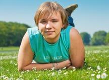 Jugendlichjunge, der auf Gras liegt Stockfotografie