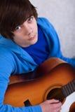 Jugendlichjunge, der die Gitarre spielt Lizenzfreie Stockfotografie