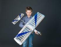 Jugendlichjunge, der ein hölzernes flaches Modell hält Lizenzfreie Stockbilder