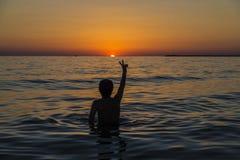 Jugendlichjunge, der im Meer bei Sonnenuntergang in Sizilien badet lizenzfreie stockfotos