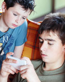 Jugendlichjungen, die auf dem Smartphone, im Freien spielen Stockbild