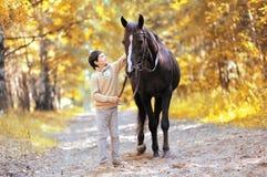 Jugendlichjungen- und -pferdegehen der Herbstsaison glückliches Stockfoto