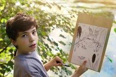 Jugendlichkünstlerjunge machen Entwurfsskizze vom Teichsee im Wald Stockbild