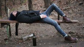 Jugendlichkranker, nachdem zu viel Alkohol, der deprimierte Kerl getrunken worden ist, der auf Bank liegt stock video footage