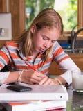 Jugendlichkursteilnehmer, der an Schuleheimarbeit arbeitet Lizenzfreie Stockfotografie