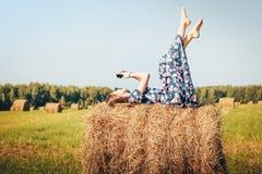 Jugendlichmädchen auf einem Herbstgebiet mit Heustapel Stockfoto