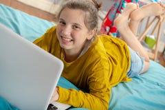 Jugendlichmädchen, das auf dem Bett, unter Verwendung eines Laptops liegt stockbilder