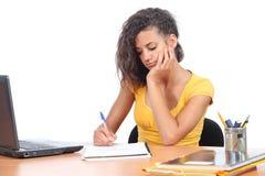 Jugendlichmädchen, das auf einem Schreibtisch studiert stockfotos