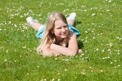 Jugendlichmädchen, das auf Gras liegt Stockfotografie