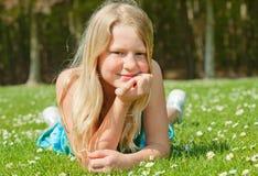 Jugendlichmädchen, das auf Gras liegt Lizenzfreies Stockbild