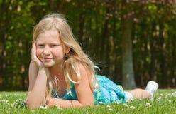 Jugendlichmädchen, das auf Gras liegt Stockbilder