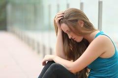 Jugendlichmädchen, das deprimiertes im Freien sitzt Stockfotografie
