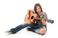 Jugendlichmädchen, das eine Akustikgitarre spielt Stockfotos