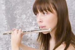 Jugendlichmädchen, das Flöte spielt stockbild