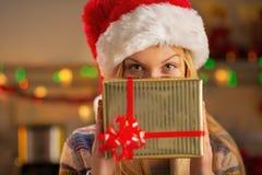 Jugendlichmädchen, das hinter Weihnachtspräsentkarton sich versteckt Lizenzfreies Stockfoto