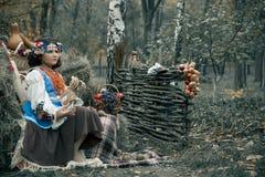 Jugendlichmädchen, das im Heu trägt einen Kranz und ein nationales ukrainisches Kostüm nahe bei dem Obstkorb sitzt Lizenzfreie Stockbilder
