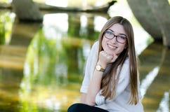 Jugendlichmädchen, das im Naturwald nahe See aufwirft Lizenzfreie Stockfotografie