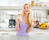 Jugendlichmädchen, das Schokoladenmuffin mit Milch isst Lizenzfreies Stockfoto
