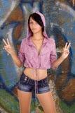 Jugendlichmädchen, das v-Zeichen auf Graffitihintergrund bildet Stockfotos