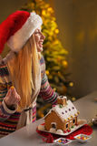 Jugendlichmädchen, das Weihnachtsplätzchenhaus verziert Lizenzfreies Stockfoto