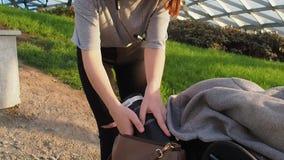 Jugendlichmädchen in einem grauen T-Shirt setzt ein Notizbuch mit Anmerkungen in eine Tasche im Park an einem sonnigen Tag ein stock footage