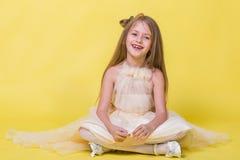 Jugendlichmädchen in einem Kleid auf einem gelben Hintergrund, der für die Kamera aufwirft und sitzt auf dem Boden Stockfoto