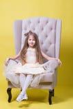 Jugendlichmädchen in einem Kleid auf einem gelben Hintergrund, der für die Kamera aufwirft und sitzt auf dem Stuhl Lizenzfreie Stockfotografie