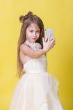Jugendlichmädchen in einem Kleid auf einem gelben Hintergrund fotografierte sich am Telefon Stockfotografie