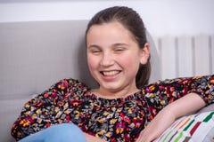 Jugendlichmädchen entspannt sich im Sofa Stockbild