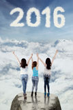Jugendlichmädchen feiern neues Jahr von 2016 auf der Klippe Stockfotografie